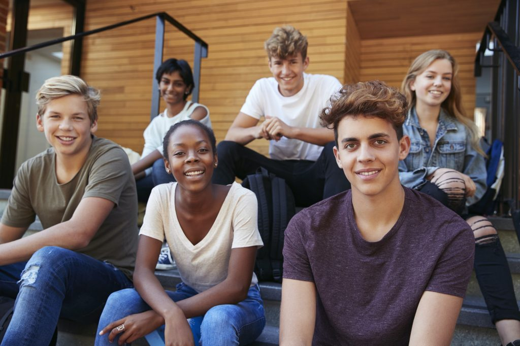 Group Of Teenage Students Socialising On College Campus Together