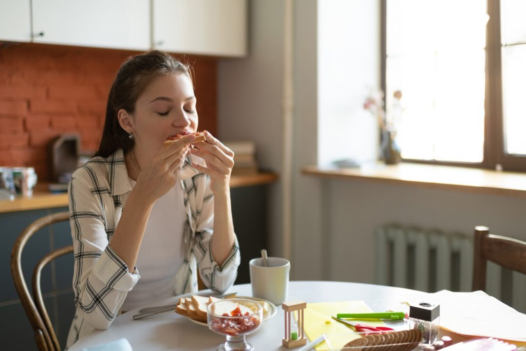 Teenage girl eating breakfast at kitchen table